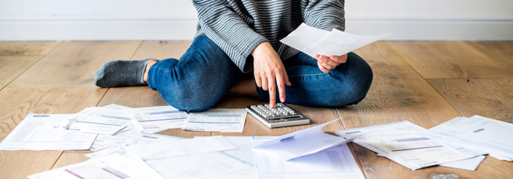 Woman sorting out bills on the floor